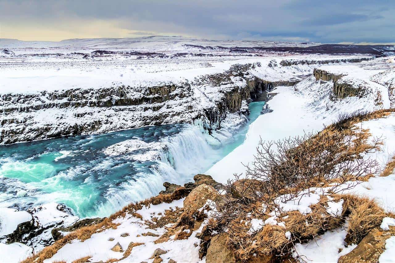 gullfoss waterfall in iceland on a cloudy winter day covered in snow