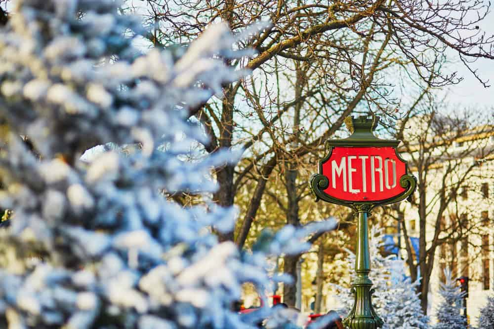 Paris metro sign with nearby tree covered in snow