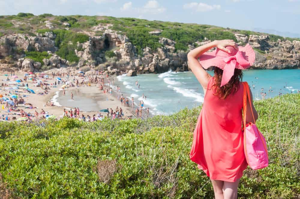 moteris, stovinti Calamosche paplūdimyje Sicilijoje, Italijoje