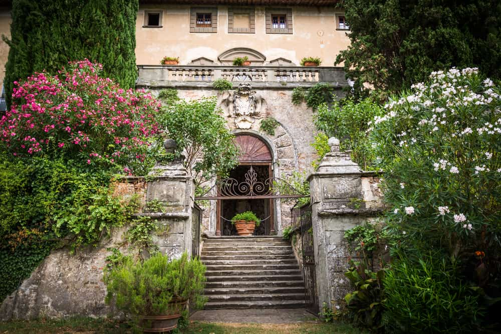 with flowers framing the lovely Castello di Montegufoni, it truly is a fairytale castle in Tuscany
