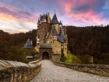 One of the most iconic castles in Germany, Burg Eltz sitting on a hill with its long walkway and purple cloudy sunset