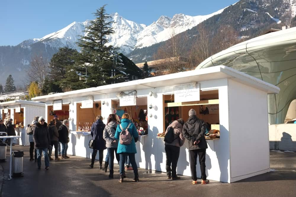 Booths of goods and a view of the alps in Hungerburg Innsbruck, one of the Christmas markets in Austria