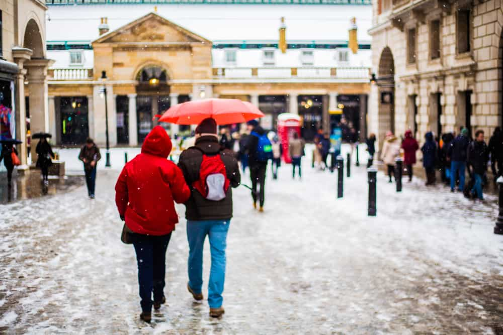 London in winter, a couple walking in a snowy Covent Garden