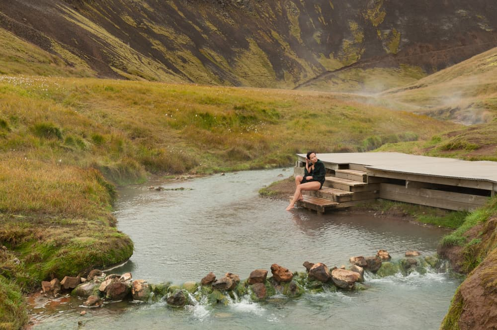 woman sits on stairs along river at Reykjadalur Hot Springs