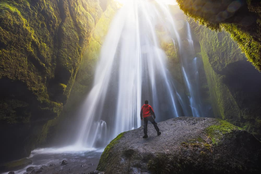 person standing at base of Gljufrabui waterfall in South Iceland