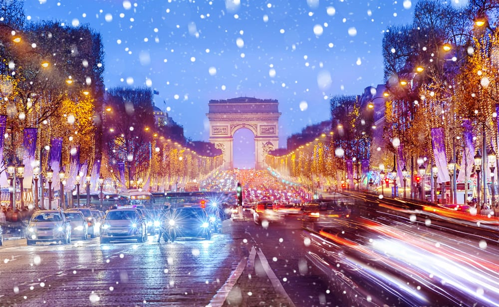 Arc De Triomphe as the snow falls during christmas in paris