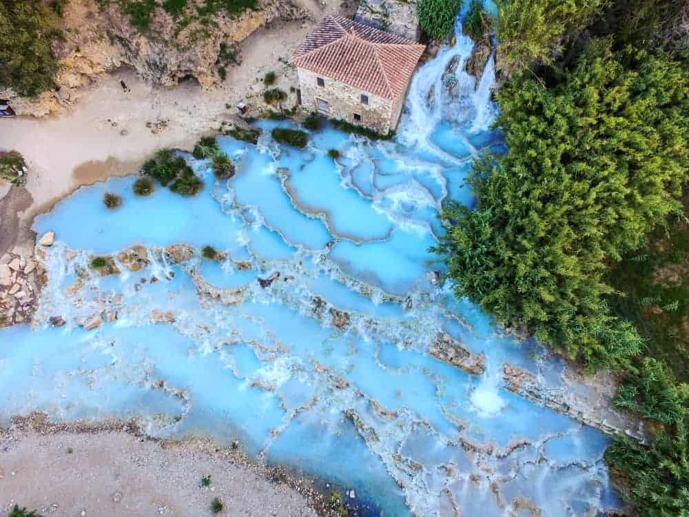 A drone view of the hot springs in Saturnia shows the multiple pools of the thermal springs and the icy blue waters.