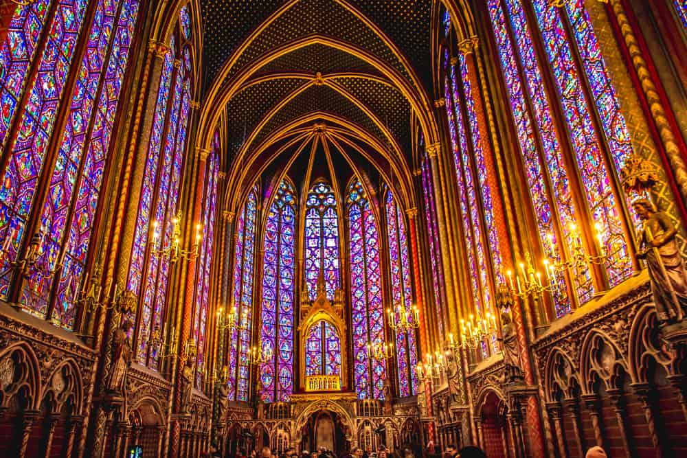 the stained glass walls of St. Chapelle Cathedral lit by candles as well as external light