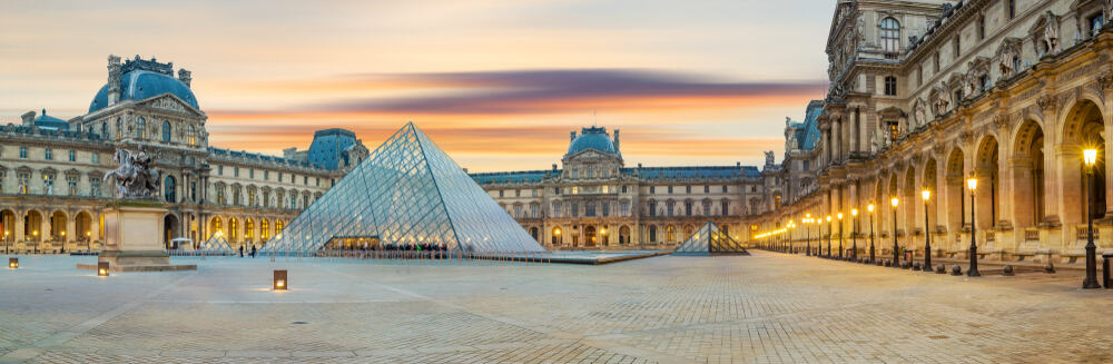 The Louvre and the Pyramid installation set against a light sunset sky