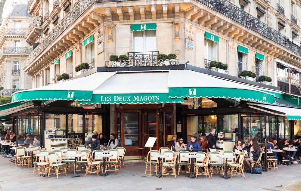 beautiful green cafe in Paris exterior with chairs