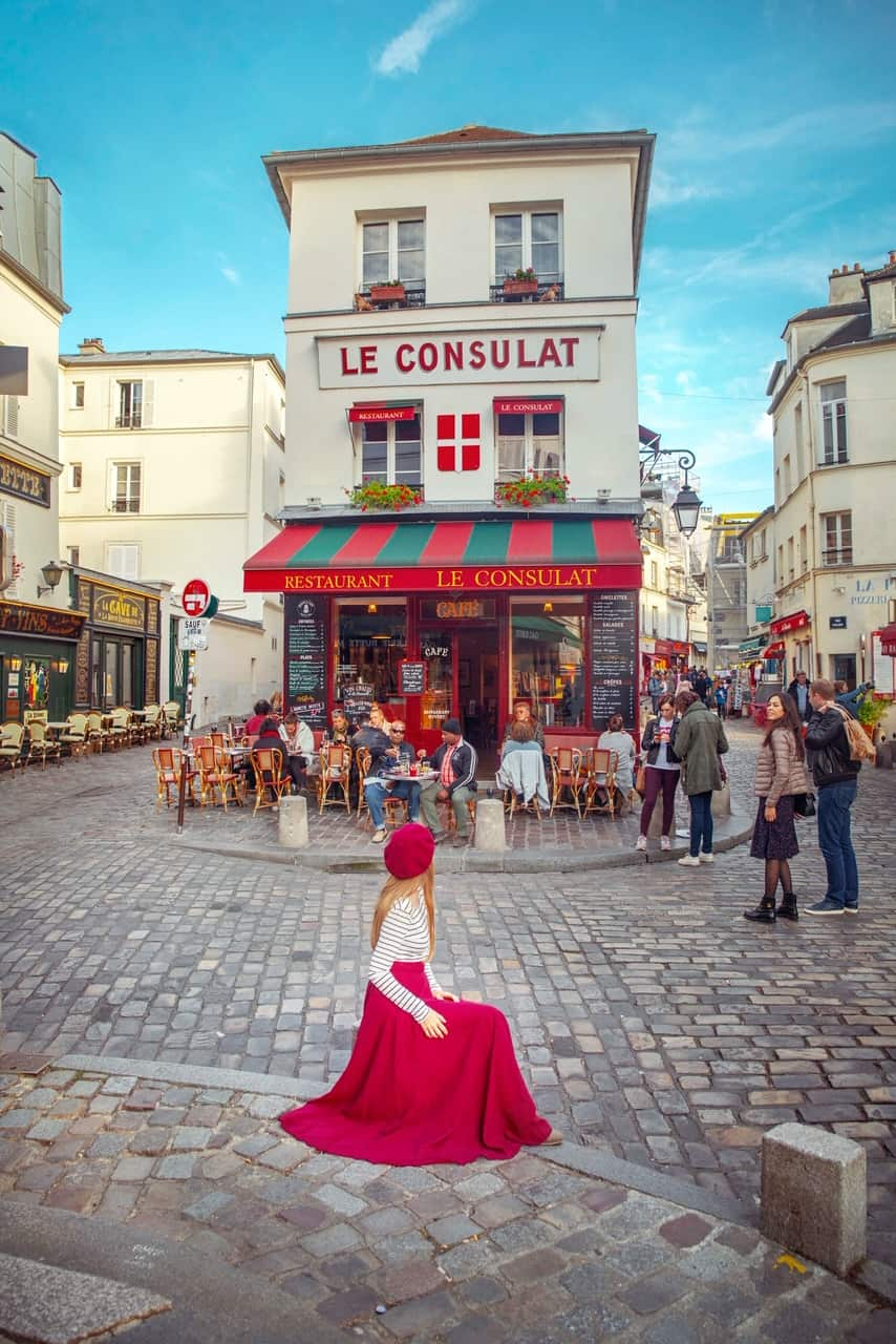 girl sitting in front of Le Consult cafe in Montmartre Paris