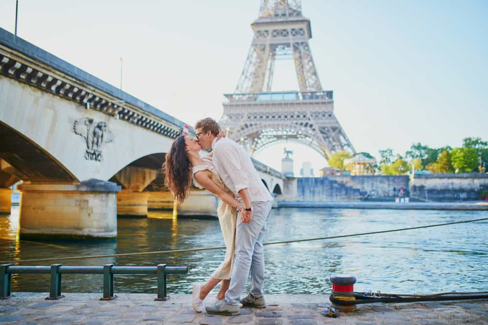 couple kissing in front of the Eiffel Tower on their paris honeymoon
