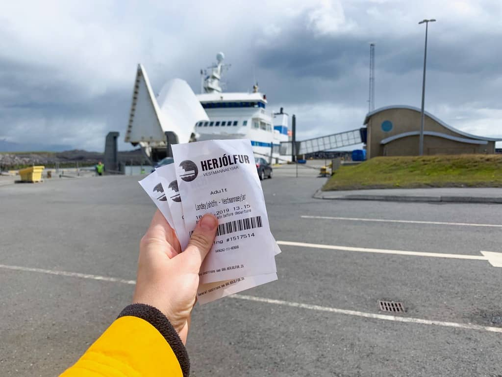 holding tickets to the westman islands ferry on the mainland