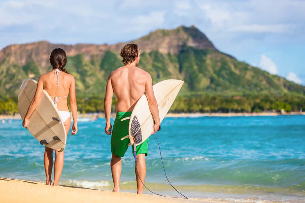 Photo of couple surfing, a great Hawaii honeymoon activity