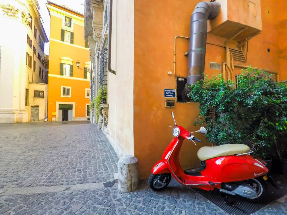 red vespa on an empty street in florence