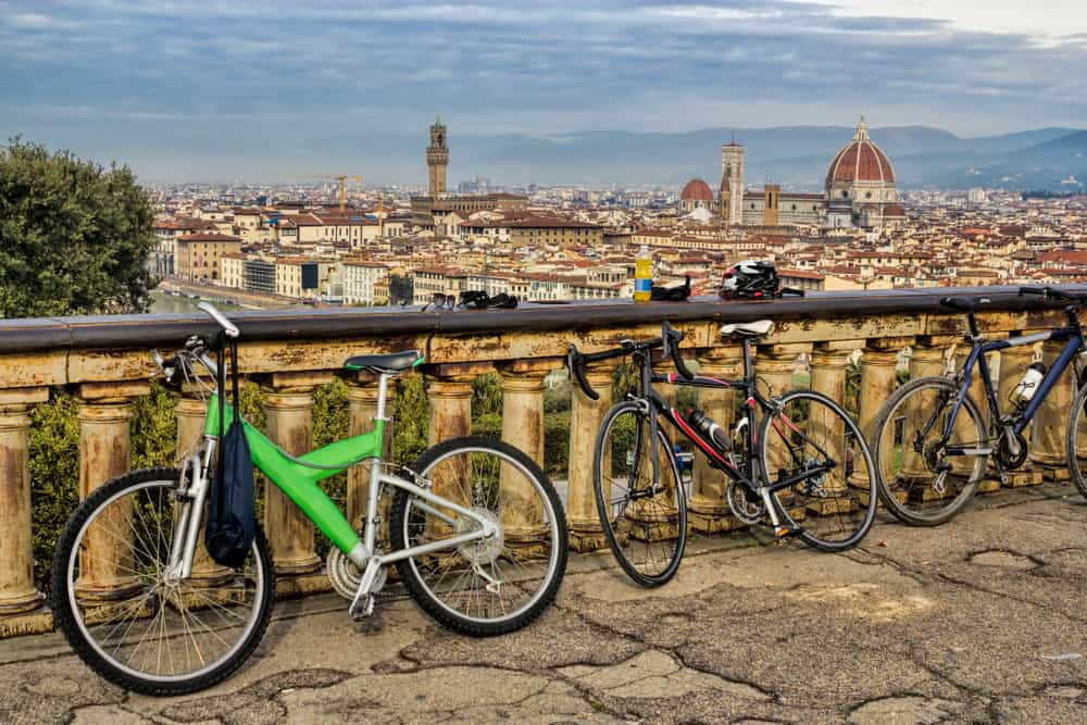 bicycles sitting against a fence looking out onto Florence