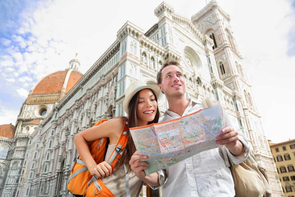 Photo of couple with a map who could be you on your Tuscany honeymoon.