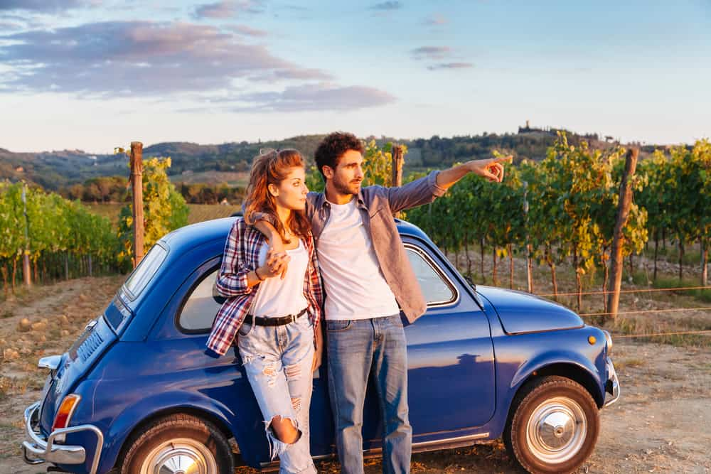 Photo of couple with a car in Italy, an excellent way to travel during your Tuscany honeymoon.