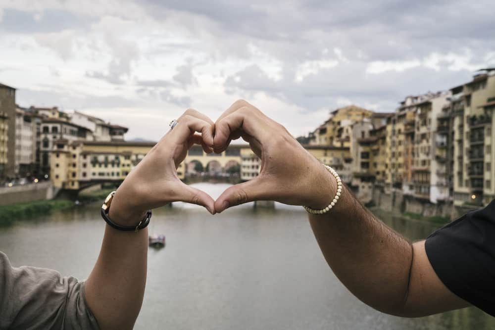 Photo of couple making a heart with their hands.