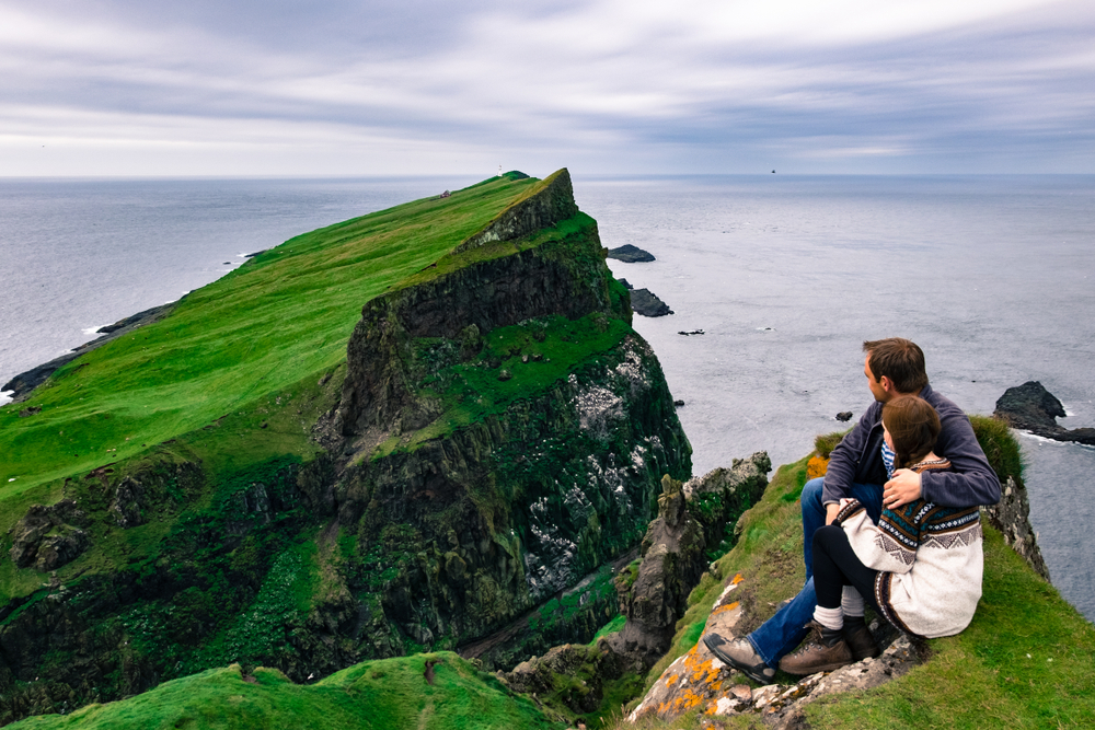 Photo of a couple overlooking cliffs in Ireland.