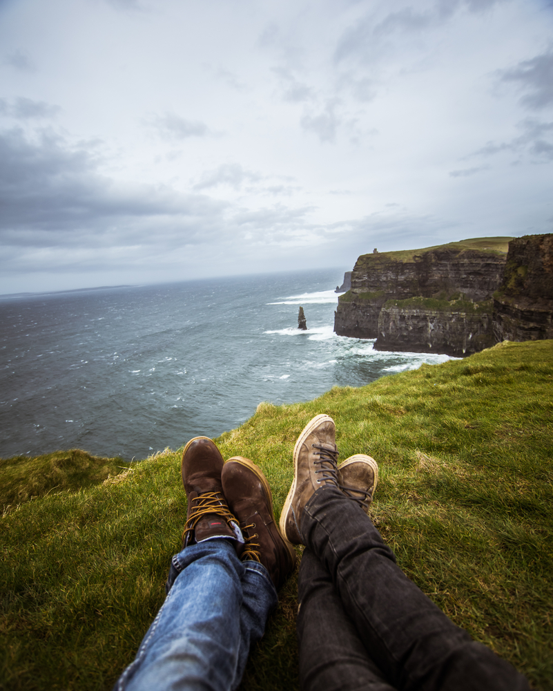 Photo of a couples' shoes, overlooking ocean.