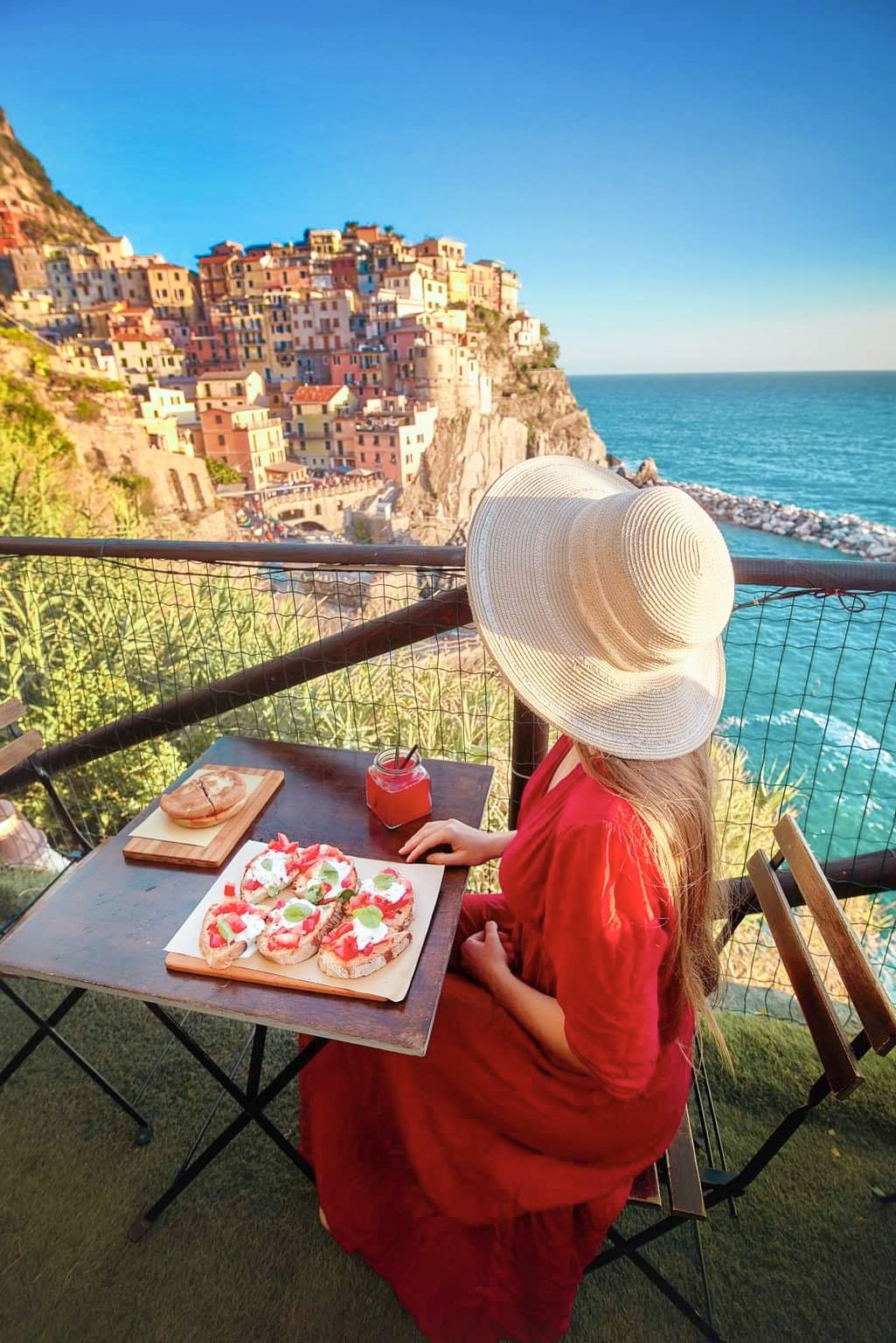 woman sitting with a colorful crostini plate in front of Cinque Terre's colorful buildings