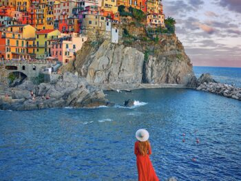 woman in red dress standing in Manarola one of the smaller cities in italy on the riviera