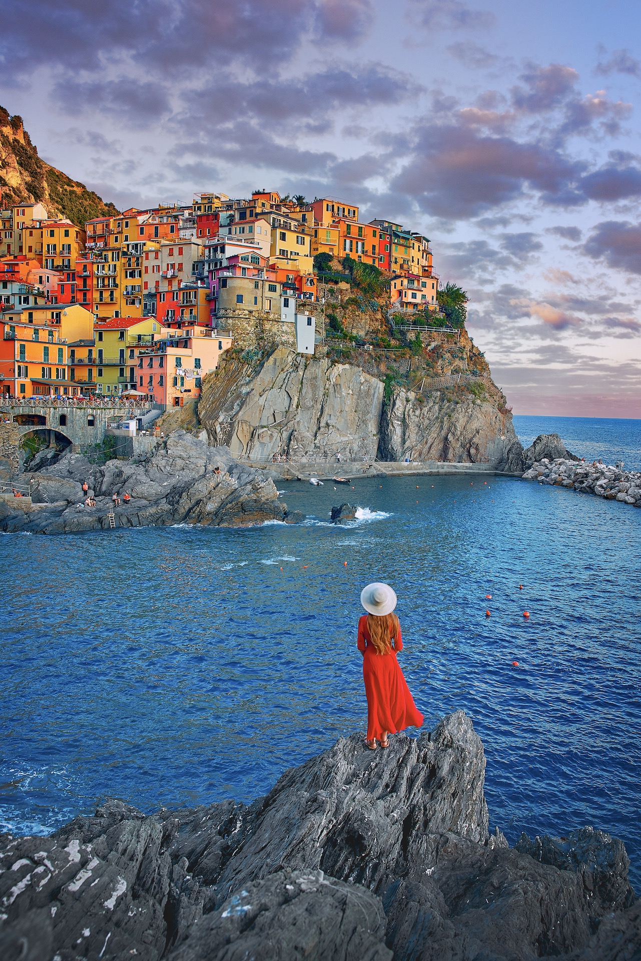 woman standing on the rocks in front of the water and colorful buildings of Cinque Terre