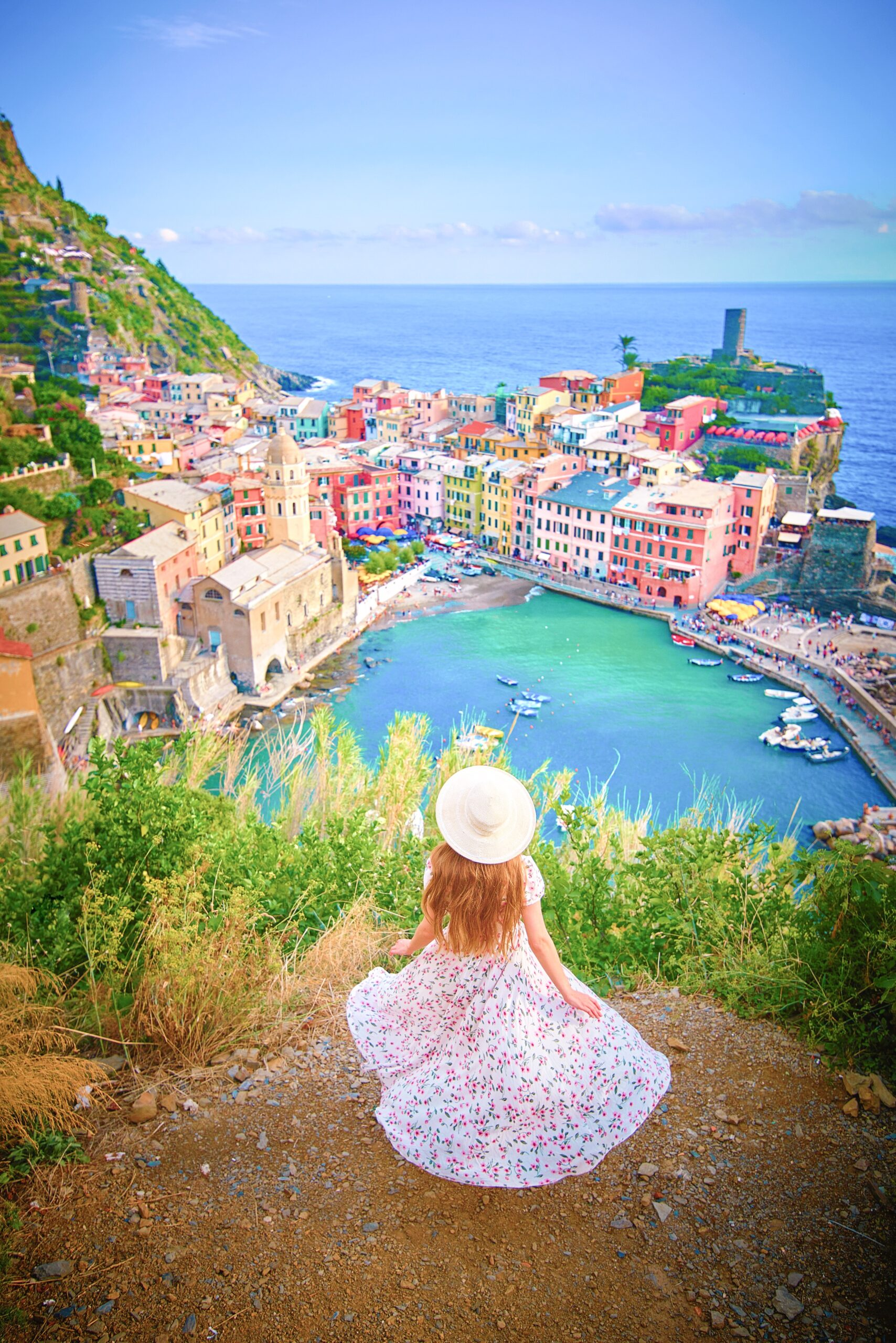 woman in flowery dress in front of teal waters and colorful buildings of Cinque Terre Northern Italy itinerary