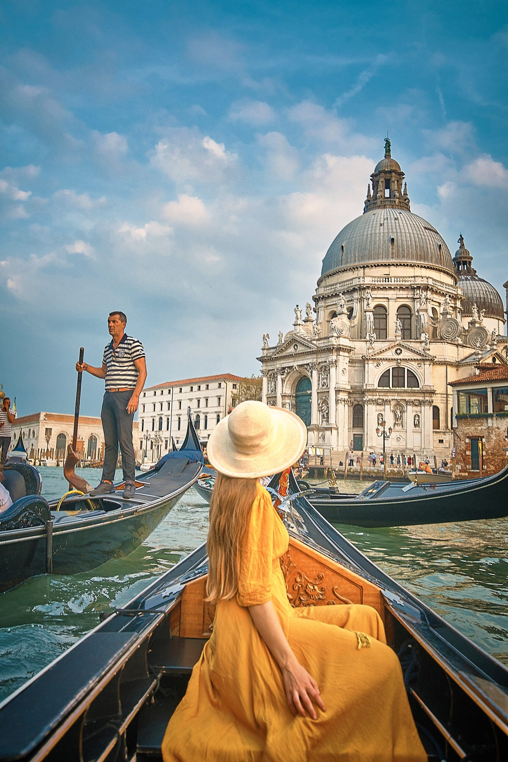 woman in golden dress in gondola floating towards basilica Northern Italy itinerary