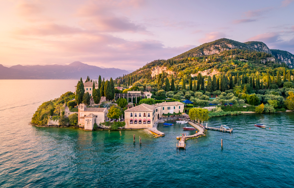 beautiful villa on Lake Garda with green mountain, blue waters, and colorful sky