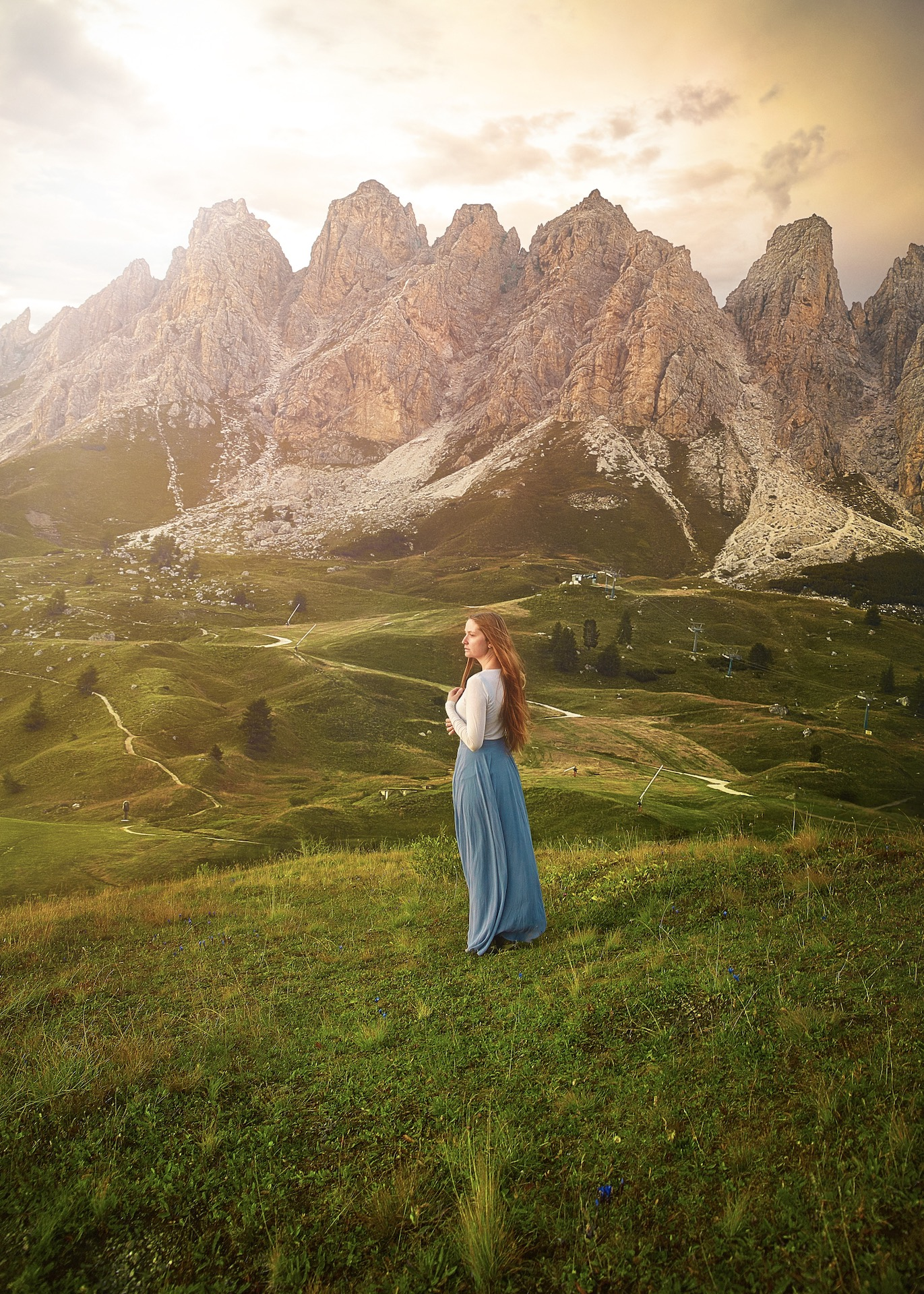 woman standing in the middle of green plains with towering mountains in the background northern Italy itinerary