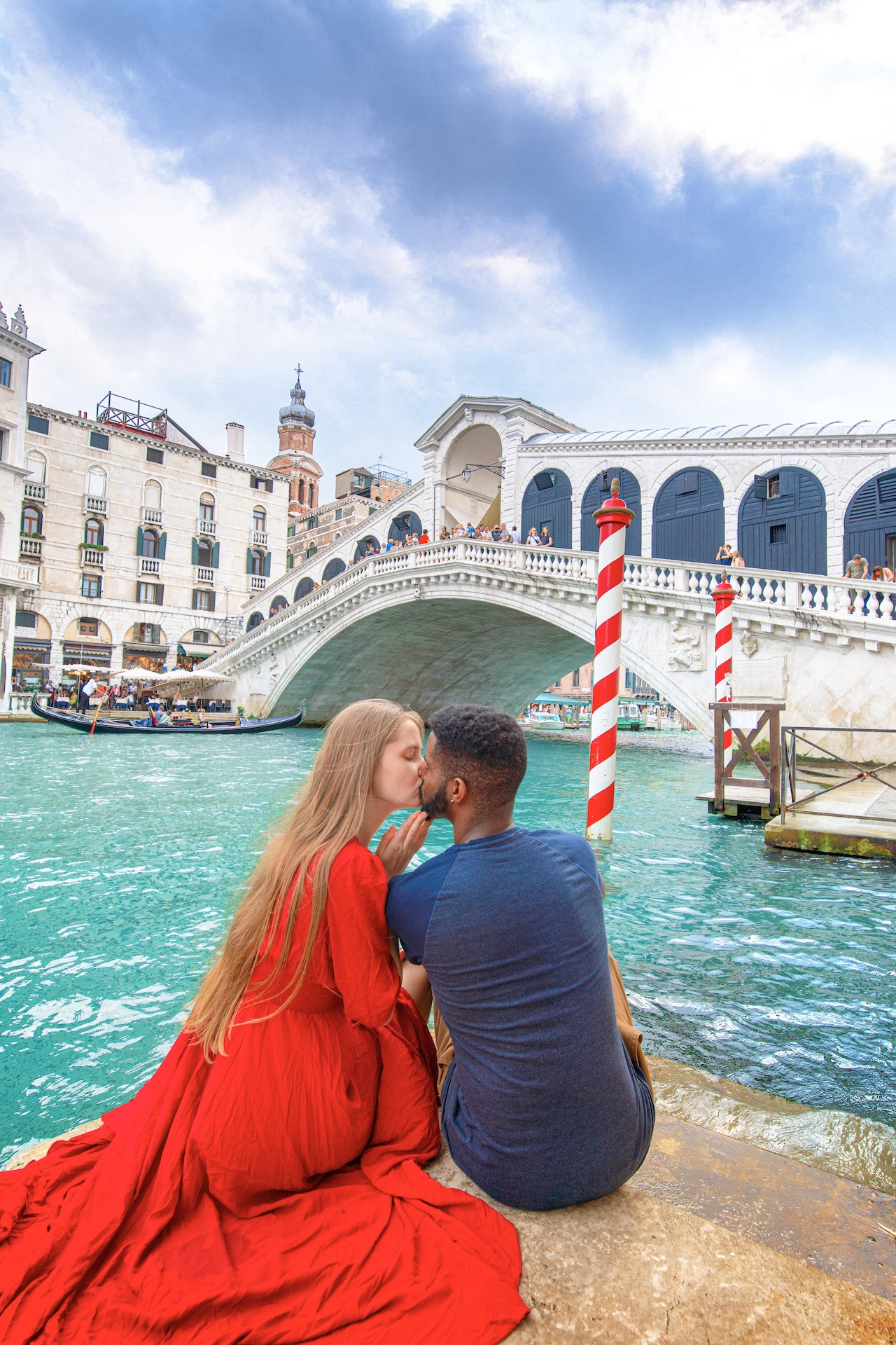 couple kissing in front of the famous Rialto Bridge in Venice