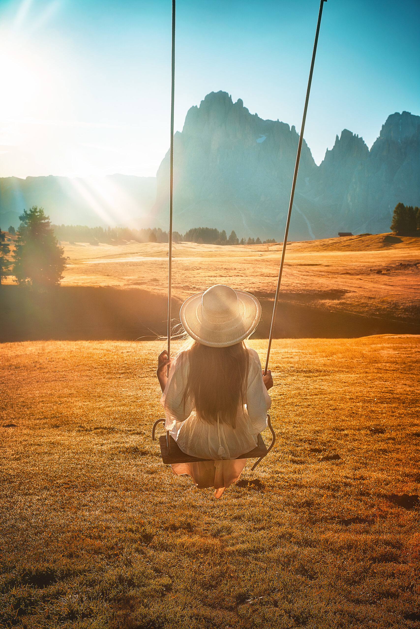 girl on swing over golden plains with rocky mountain in background