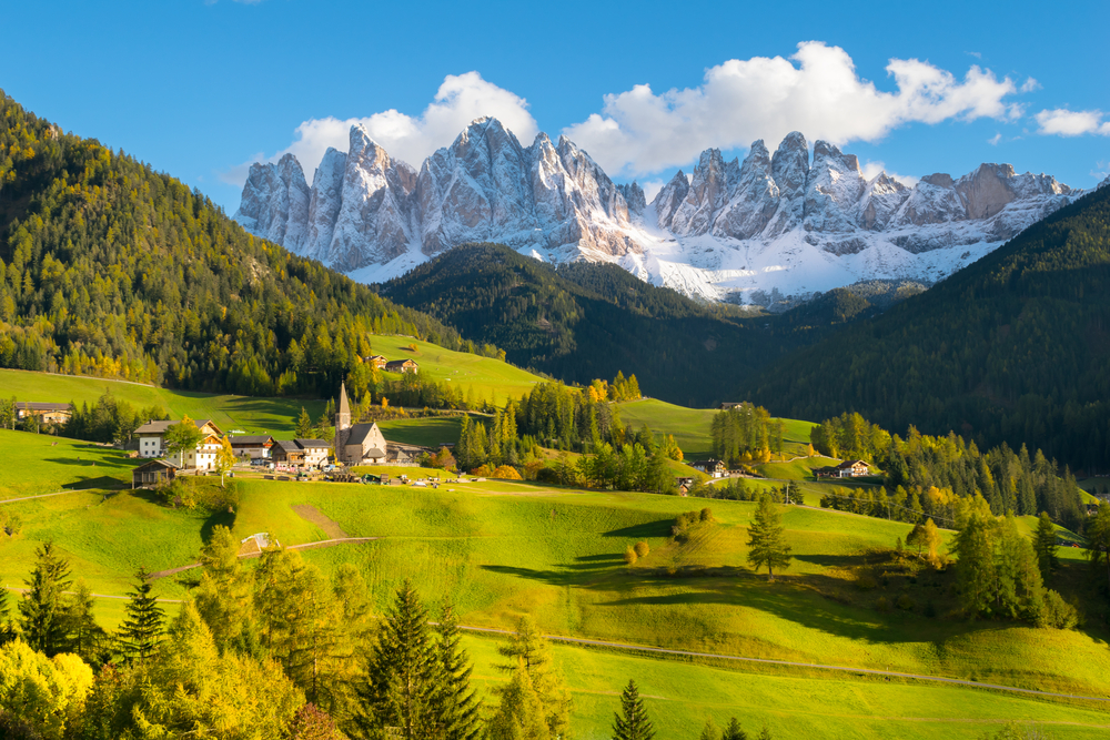 snowy mountains behind bright green valley Northern Italy itinerary