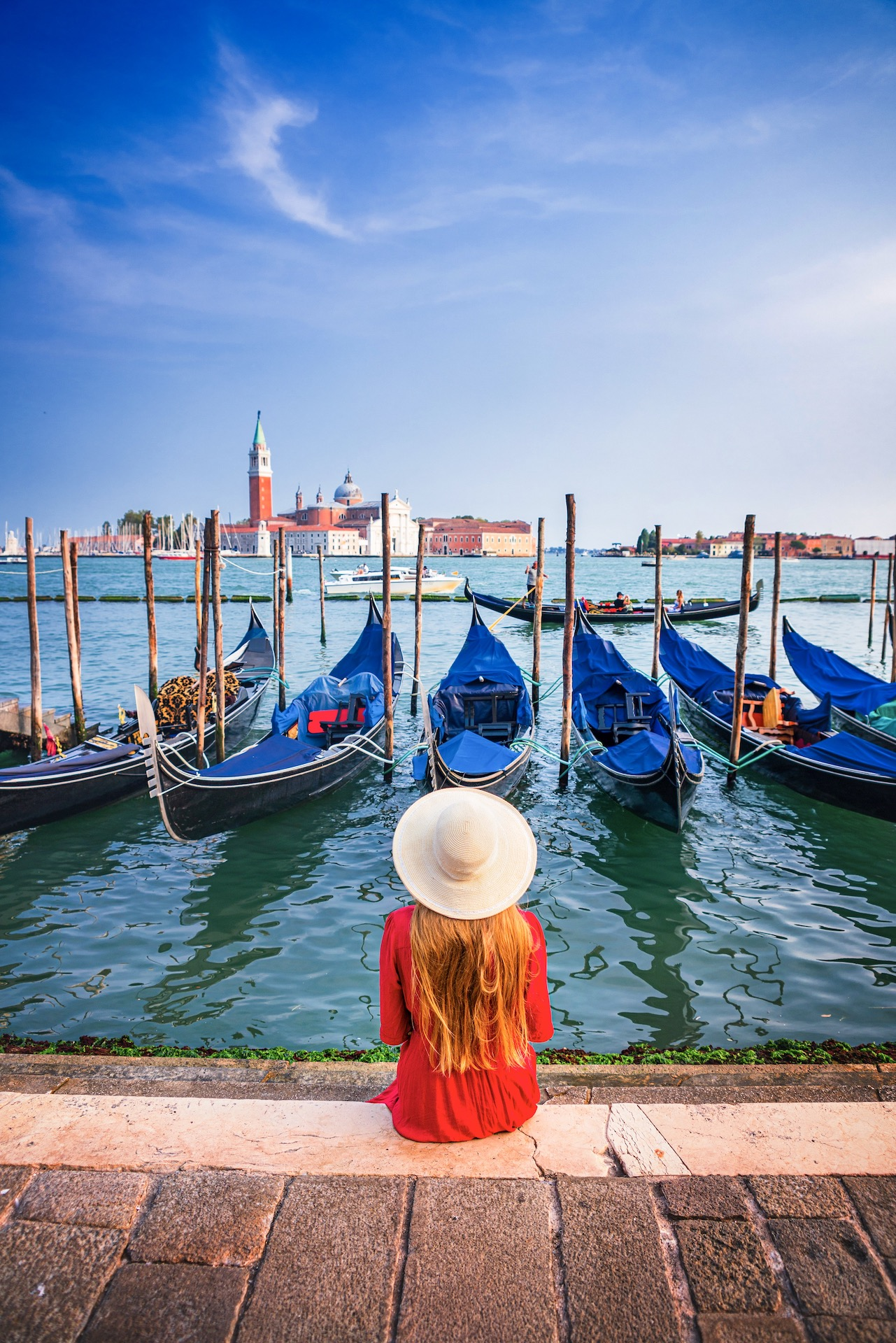 woman in red dress sitting along Venetian canal lined with gondolas Northern Italy itinerary