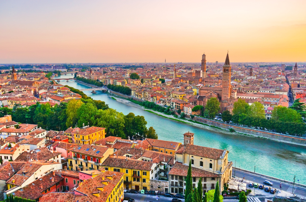 aerial view of the red-roof buildings of Verona with a river cutting through it at sunset