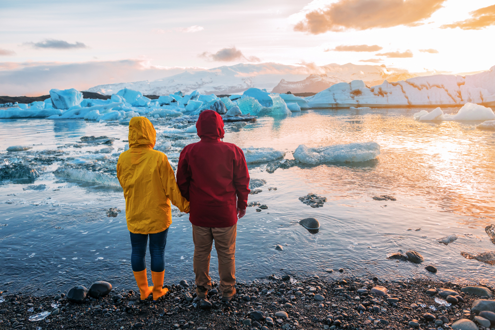 Photo of couple standing in front of a glacier in Iceland.