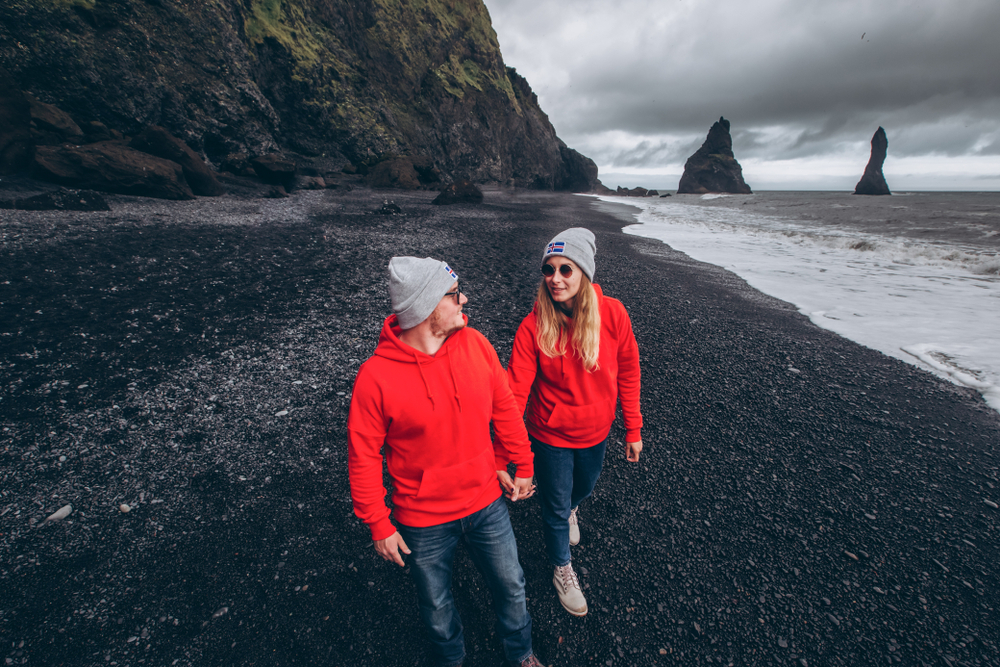Photo of couple at one of Iceland's famous black sand beaches.