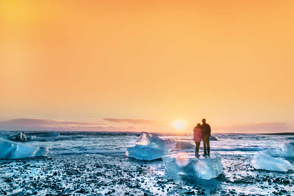 Photo of couple standing on ice melts in Iceland.