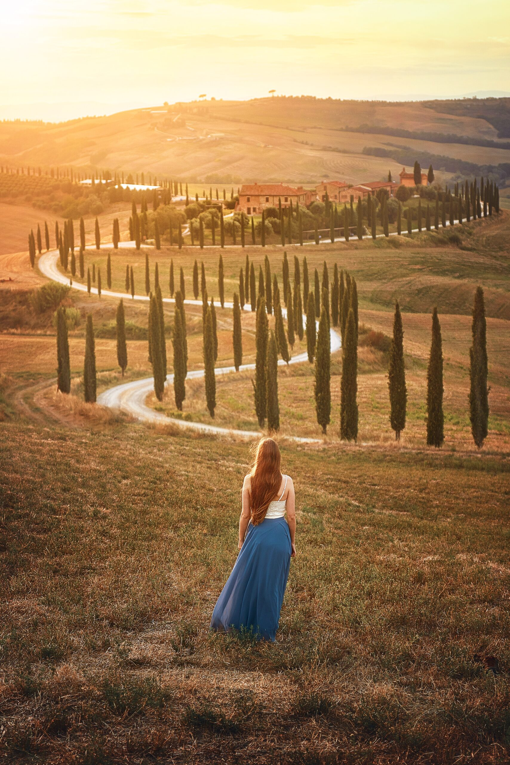 Tree Tunnel in Tuscany at Sunset is one of the best Instagram spots in Tuscany Italy | prettiest views in Tuscany | pretty instagram spots in Tuscany Italy | Tuscany travel tips | Victoria Yore of Follow Me Away standing in the Tuscany Countryside near a remote road and tree lined path. One of the best Tuscany photography locations