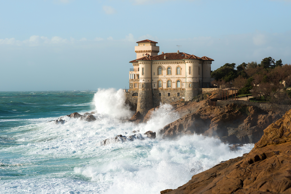 waves crashing into castle by the water