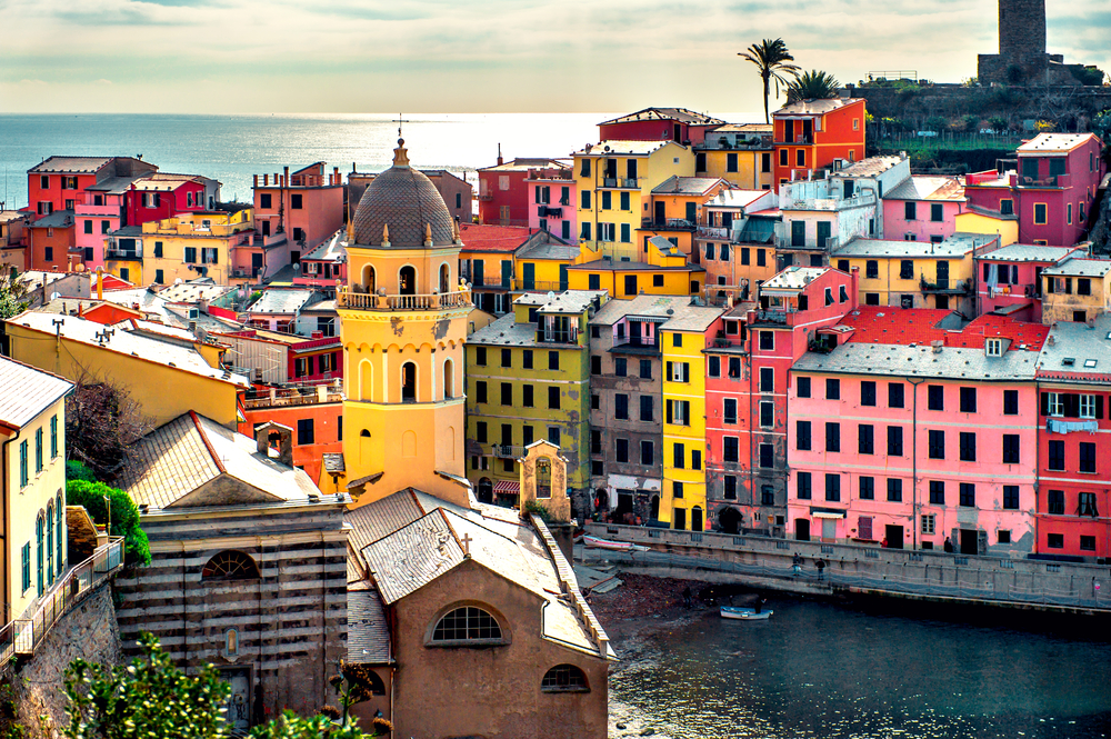 view of colorful Cinque Terre buildings with yellow tower in front