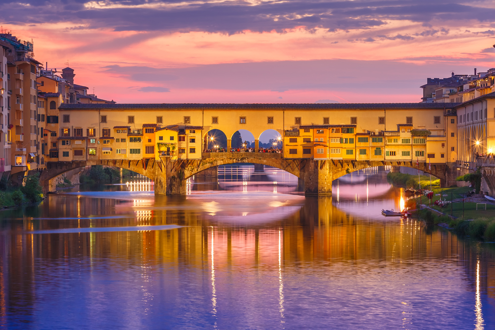 moody, sunset-tinted view of Ponte Vecchio bridge over river