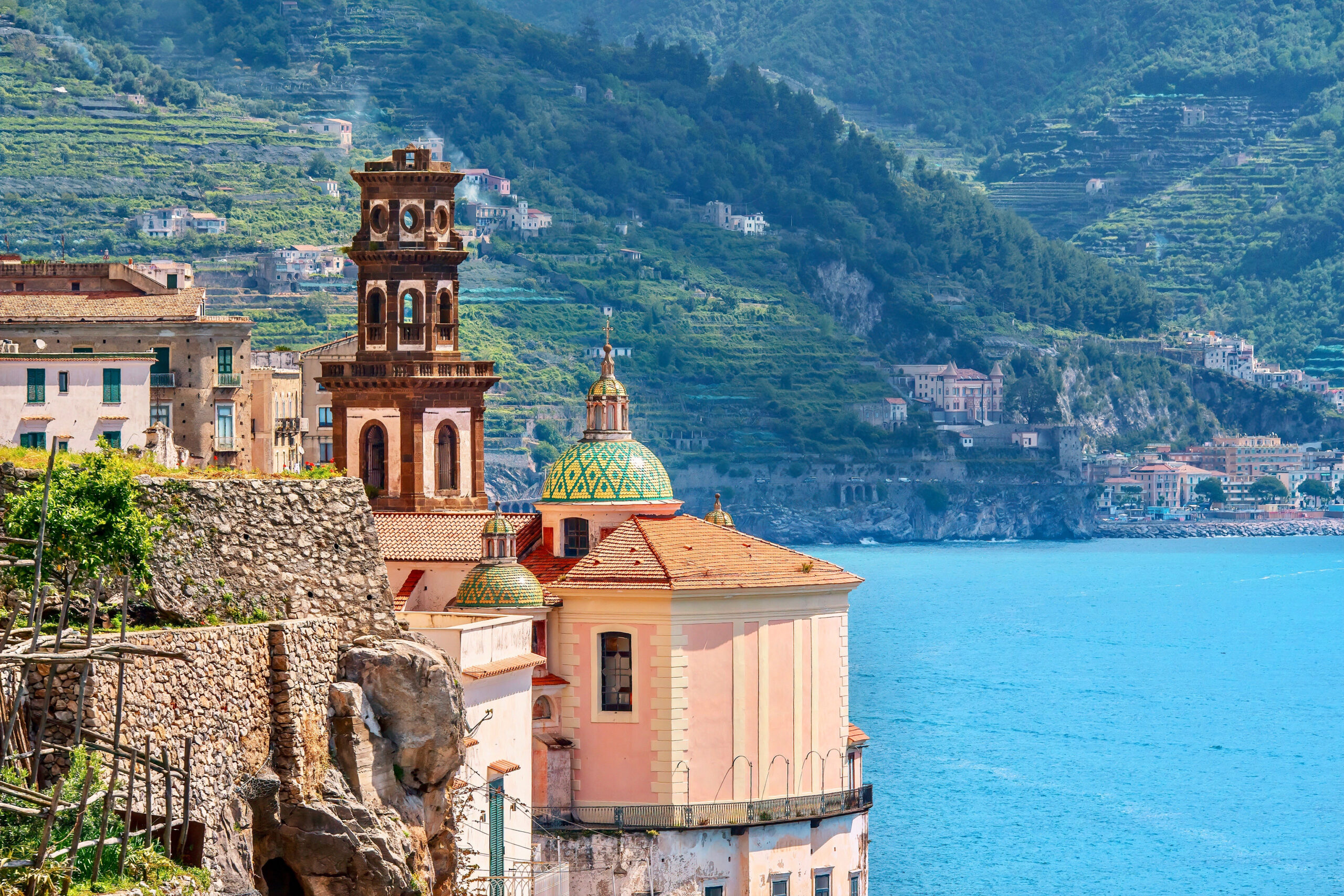 Photo of Castiglione di Ravello beach. A bell tower is shown next to an exquisite green and yellow majolica tiled dome church. Light blue water and green mountains are seen in the background.