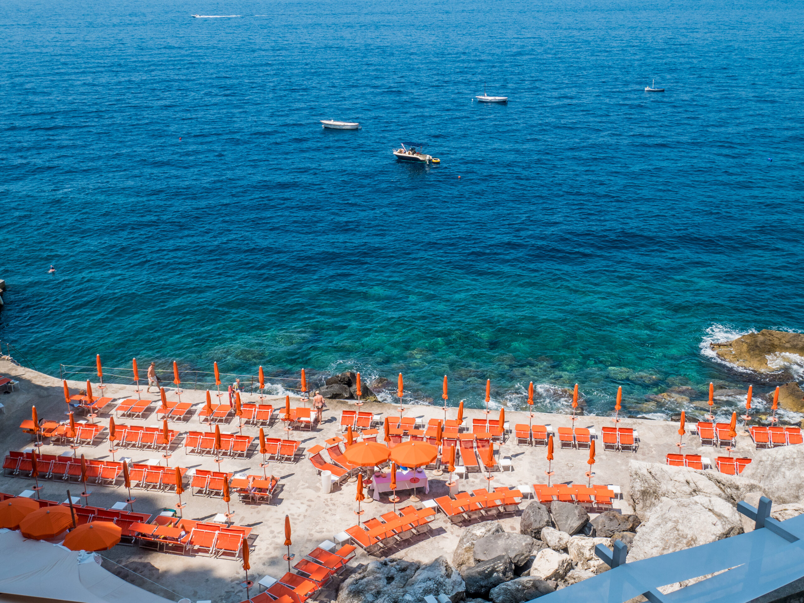 Photo of Gavitella Beach, one of the more secluded Amalfi Coast beaches. Orange colored umbrellas and bold blue water is pictured.