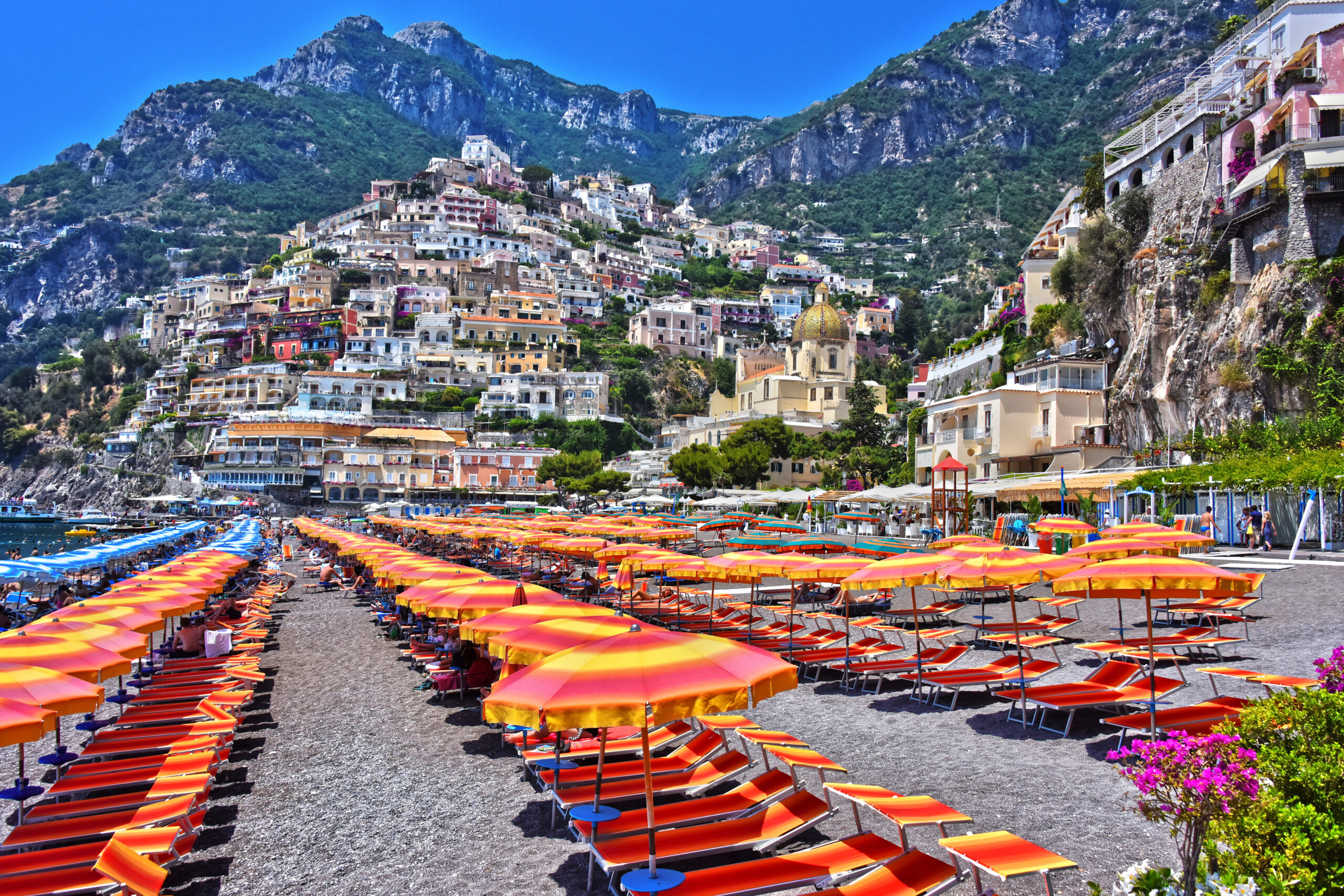 Photo of Marina Grande of Positano on the Amalfi Coast. Orange, yellow, and pink umbrellas are in the forefront with rocky cliffs in the background.