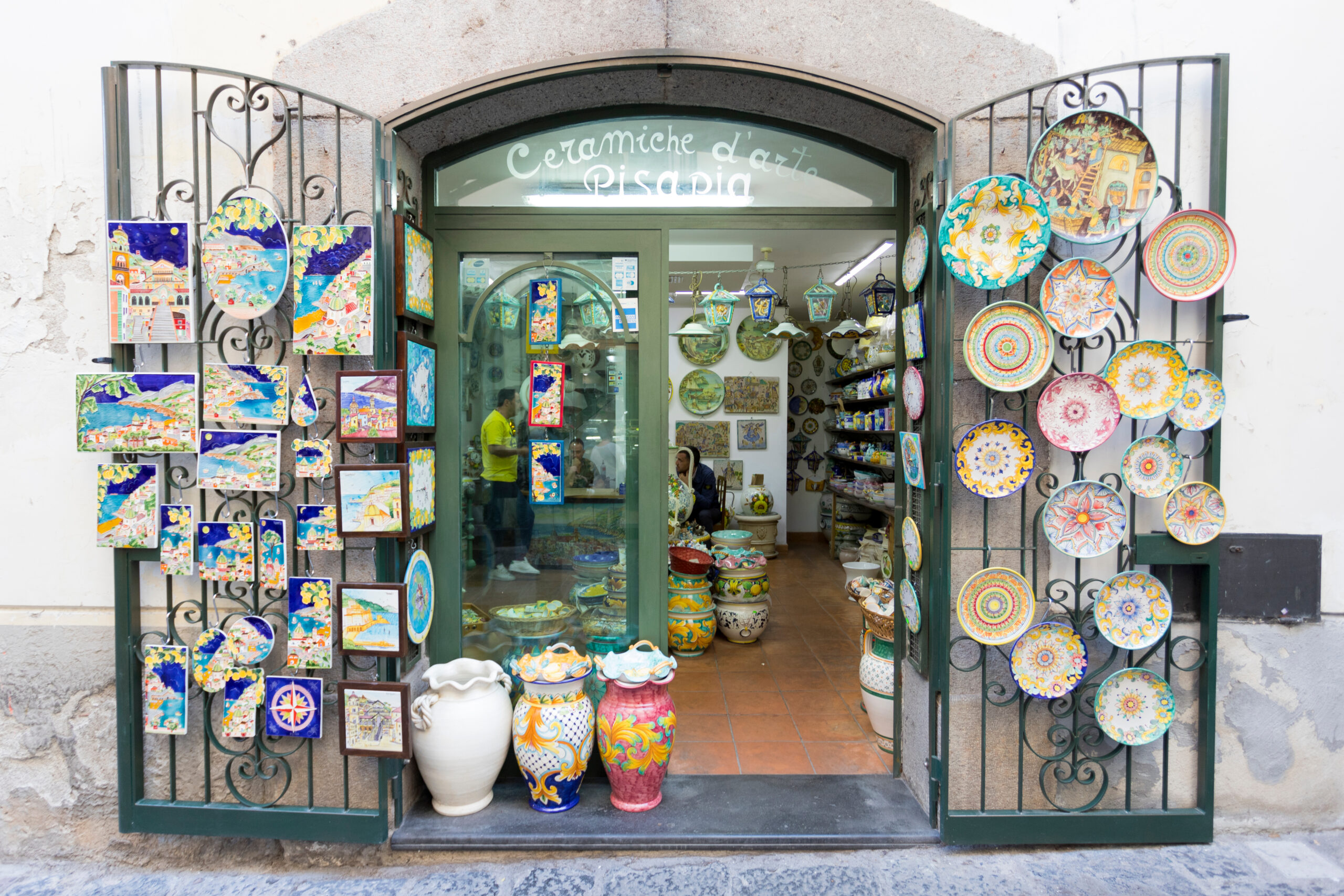 Photo of majolica ceramics found in Vietri sul Mare, one of the best Amalfi Coast beaches for unique souvenirs. Plates, wall hangings, and vases are being displayed in a store front.
