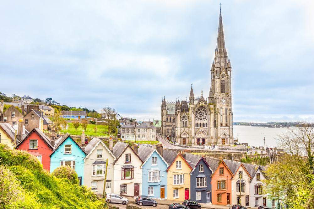 The brightly colored Deck of Cards houses in Ireland stacked on a steep hill with a Cathedral behind.