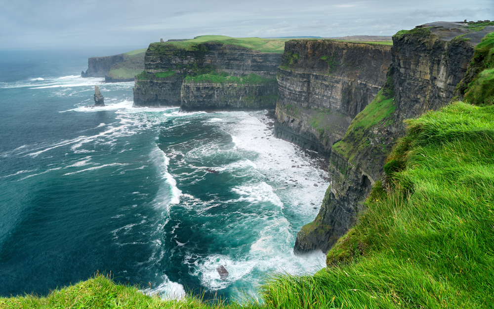 sheer cliffs of Moher with roaring ocean and mist day trips from Dublin
